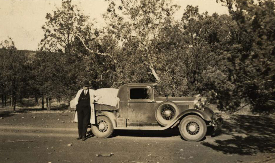 Australian Inland Mission Southern Patrol car with Reverend John Flynn leaning against the back tray